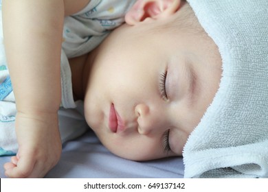 Asian baby boy get sick,he has got fever,running nose and hi fever,flu,sleeping on parent bed. He has wet small towel on his forehead.Poor baby catch cold from his sister who went to school.