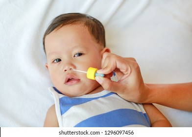 Asian baby boy gets nose drops. Baby care concept.