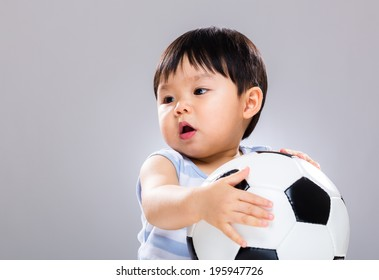 Asian baby boy holding soccer ball