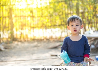 Asian baby boy  holding  training cup  sitting alone against the light
