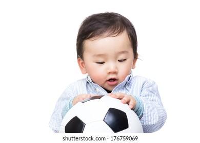 Asian baby boy looking at soccer ball