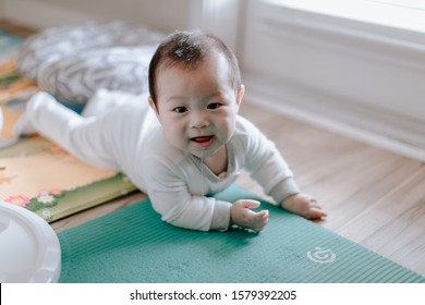 Asian baby boy lying on play mat with toys during tummy time at home. Child is 6 months old.