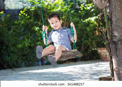 Asian baby boy playing on a swing and having fun in park