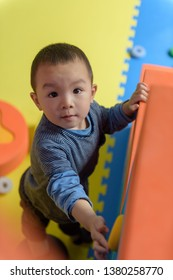 Asian baby boy playing with plastic building blocks toys in indoor playground