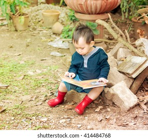 Asian baby boy reading tale book ,kid wear red boot sitting on a log