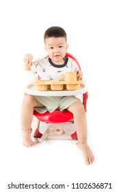 ASian baby boy sitting on the chair while eat and drink his meal time