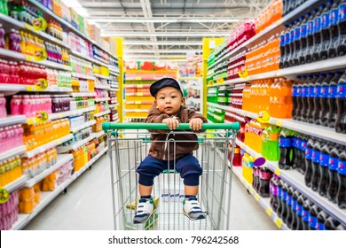 Asian baby boy sitting on the trolley while shopping aisle in the supermarket. Little kid on the shopping cart while buying groceries in the store. Concept of breastfeeding early childhood development