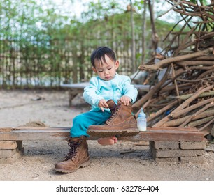 eb462dbe4 Asian baby boy try to wearing father boots while drinking milk from bottle