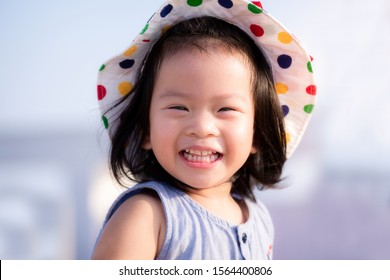 Asian baby child girl beaming smiling. Close up happy face. Little girl wearing white hat. Half body photo. She has tooth decay. Baby age 2 years and 9 month old.