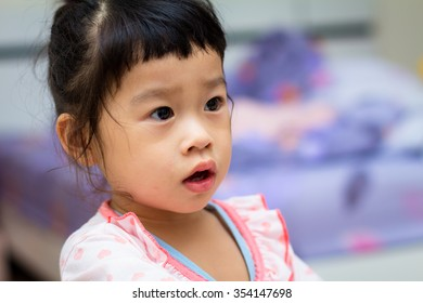 Asian baby cute girl with curly hair in the bedroom