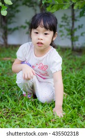 Asian baby cute girl with curly hair in the home garden