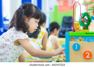 Asian baby cute girl with curly hair in the toy city