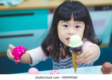 Asian baby cute girl with curly hair play make the ice cream