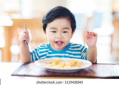 Asian baby eating a breakfast and smiling on a table, this immage can use for food, healthy, kid, boy, food, child and family concept