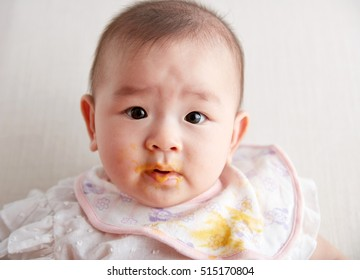 Asian baby eating food supplement, in the studio