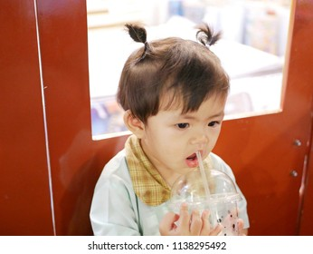 Asian baby girl, 16 months old, did not put a straw into her mouth properly, as she is still learning to drink water from a straw