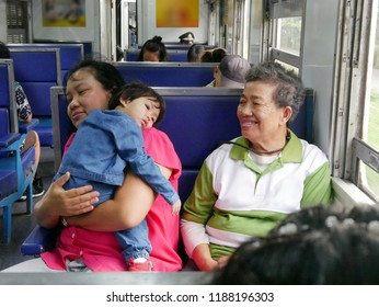 Asian baby girl, 18 months old, leaning on her auntie's shoulder while having her grandmom sitting next to and smiling at her during a long trip by train