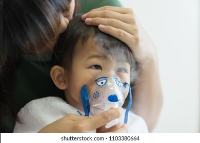 Asian baby girl breathing treatment with mother take care, at room hospital, close up health care kid concept sunny light background.