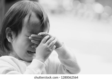 a Asian baby girl crying on the road. white background. black and white