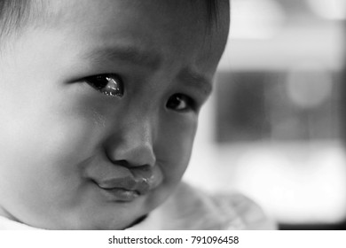 a Asian baby girl crying on a car. black and white