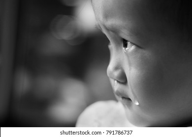a Asian baby girl crying on a car. close up. black and white