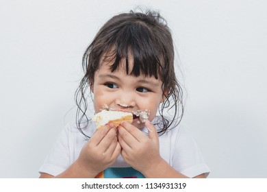 Asian baby girl eating dessert and dirty around mouth