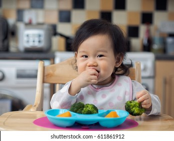Asian baby girl eating  vegetable at home kitchen