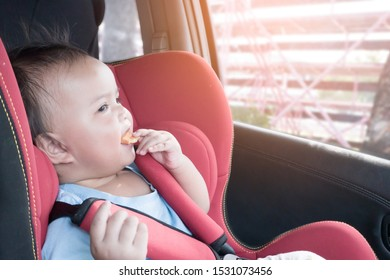 Asian baby girl enjoy eating snack and sitting on car safety seat during drive. One girl sit in safety seat with properly safety belt.