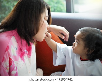 Asian baby girl feeding snack to mother with love.