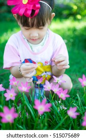 Asian baby girl with flower in garden