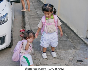 Asian baby girl holding and pulling her younger sister's hand to step up onto a pavement - children's development by allowing them be in a situation that they can express their empathy with each other