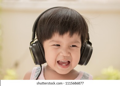 Asian baby girl listening to music with black headphone. She was smiling happily.