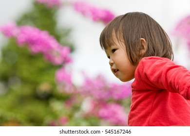 Asian baby girl looking forward with flowers in background playing at the playground in the Club at Aruja, Brazil
