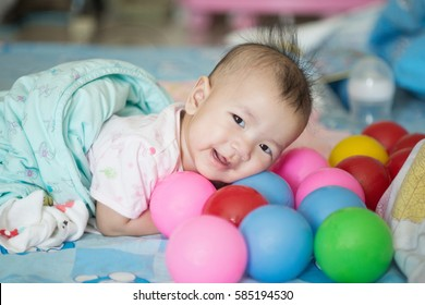 Asian baby girl lying on the tummy and playing football for kids and smiling.