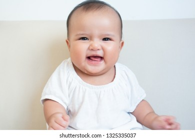 Asian baby girl making facial expression of happiness