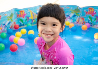 An asian baby girl in pink suit playing water and colorful balls in blue kiddie pool. She's smiling, happy and having fun
