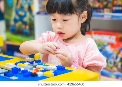 Asian baby girl play colorful plastic toy blocks