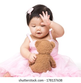 Asian baby girl play with doll