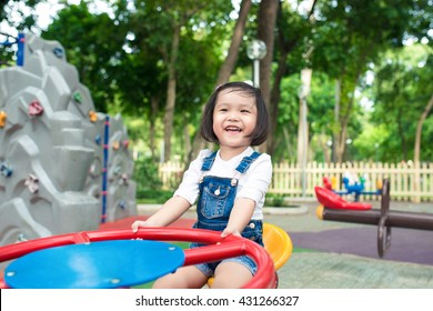 Asian baby girl playing on a swing and having fun in park