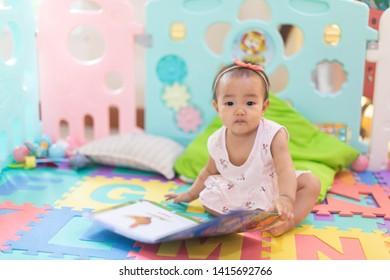 Asian baby girl reading book