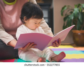Asian baby girl reading book with mom