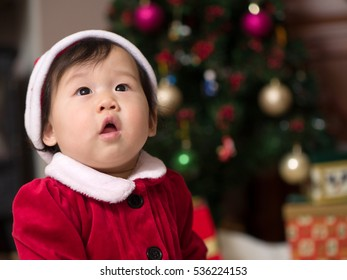 Asian baby girl in a Santa costume looking up