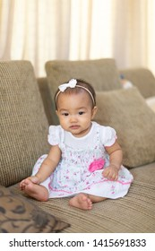 Asian baby girl sitting on the sofa