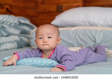 Asian baby girl teething and drips saliva while on bed.