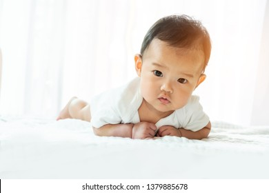 Asian baby girl upside down on the white bed At 4 months old