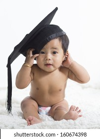 Asian baby girl wearing a graduation black cap with a tassel on a white isolated background.