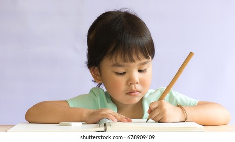 Asian baby girl write book on wooden table white background. Education concept.