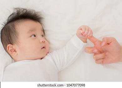 asian baby handles mom' finger