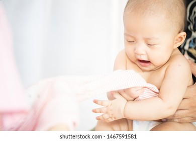 Asian baby happy in the room.Asian baby girl lying down on bed .Baby read book and play toy.