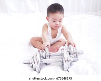 An Asian Baby Has Weight Exercise With Dumbbells.